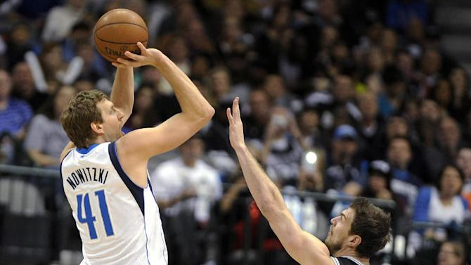 Dallas Mavericks forward Dirk Nowitzki (41) shoots over San Antonio Spurs center Tiago Splitter (22) during the first half of an NBA basketball game, Thursday, Dec. 26, 2013, in Dallas