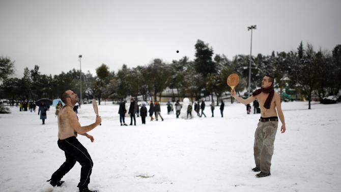 Men play a bat and ball game after a snowstorm at a park in Jerusalem
