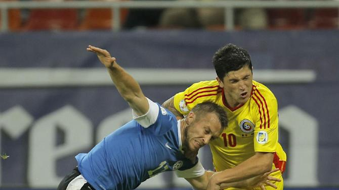 Enar Jaager, left, of Estonia and Cristian Tanase, right, of Romania challenge for the ball during the World Cup Group D qualifying soccer match at the National Arena stadium in Bucharest, Romania, Tuesday, Oct. 15, 2013