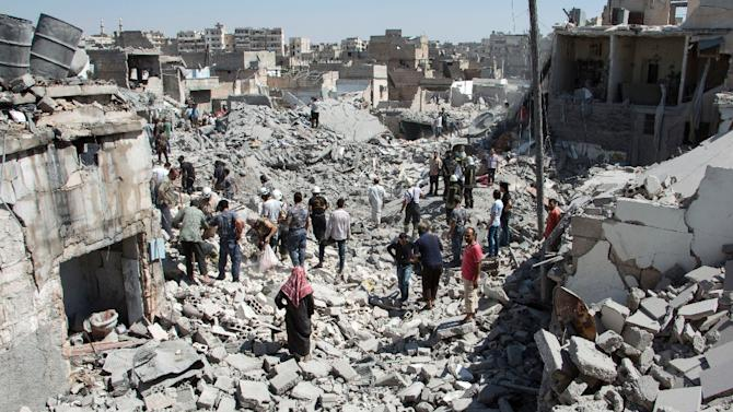 Syrians stand on the rubble of buildings after a missile fired by Syrian government forces hit a residential area in Aleppo on July 21, 2015