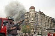 A security official stands in front of a burning section of The Taj Mahal hotel in Mumbai on November 29, 2008. Indian police have arrested a key suspect accused of coordinating the 2008 Mumbai terror attacks in which 166 people were killed and more than 300 wounded, the government said Monday