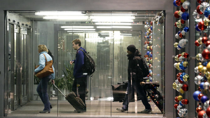 Passengers walk through Terminal 3 at O'Hare International Airport in Chicago on Saturday, Dec. 21, 2013. The National Weather Service issued a hazardous weather outlook for north central Illinois, northeast Illinois and northwest Indiana on Saturday morning. (AP Photo/Nam Y. Huh)
