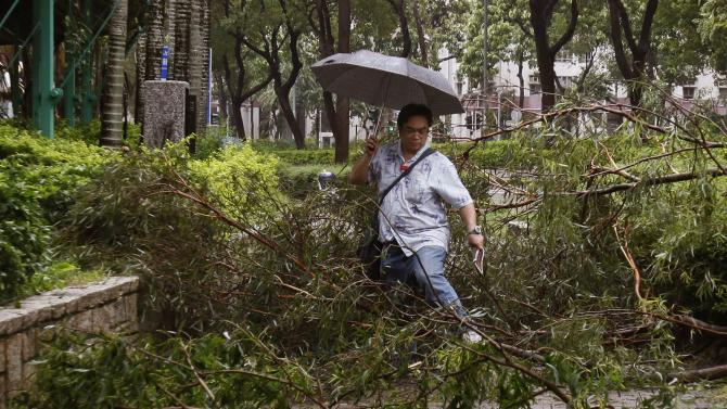 A man walks over fallen branches on a pavement at a residential district after Typhoon Usagi hit Hong Kong