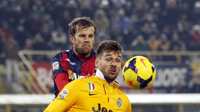 Juventus' Llorente is challenged by Bologna's Antonsson during their Italian Serie A soccer match at the Dall'Ara stadium in Bologna