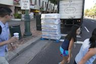 People walk past a pallet of bottled water being delivered to a shop in Waikiki in Honolulu on Thursday, Aug. 7, 2014. With Iselle, Hawaii is expected to take its first direct hurricane hit in 22 years. Tracking close behind it is Hurricane Julio. (AP Photo/Marco Garcia)