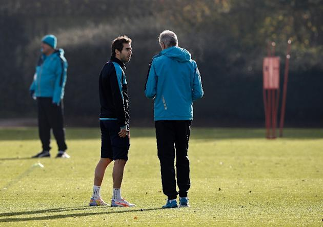 Arsenal's manager Arsene Wenger (R) talks with Mathieu Flamini who is expected to make only his second Premier League start of the season when the Gunners take on Norwich