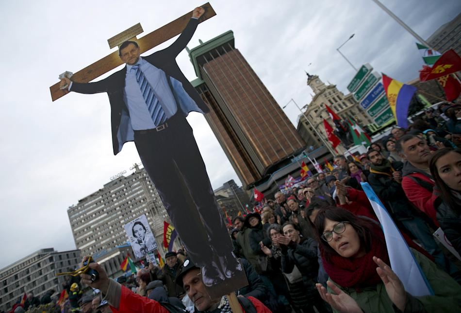 A protester holds up a cut-out image depicting Spain's PM Rajoy on a crucifix during an anti-austerity demonstration in central Madrid