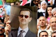 A Syrian protestor holds up a picture of President Bashar al-Assad during a pro-government demonstration outside the Syrian Central Bank in Damascus. Twin blasts targeting security buildings killed more than 20 people in the northwest Syrian city of Idlib, a monitoring group said, as the chief UN monitor presses both sides to end more than 13 months of violence