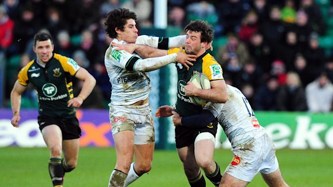 Pierre Bernard of Castres Olympique (2R) tackles Ben Foden (R) of the Northampton Saints during the Heineken Cup Round 4 re-match at Franklin's Gardens in Northampton on 18 December 2011.  AFP PHOTO / LEON NEAL (Photo credit should read LEON NEAL/AFP/Getty Images)