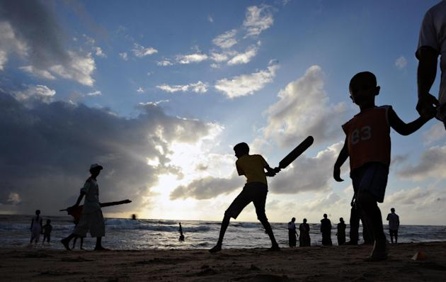 Sri Lankan children play cricket on a be
