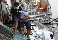 People carefully avoid the dirty water along an alley as they leave their makeshift homes, after super typhoon Haiyan battered Tacloban City, in central Philippines November 13, 2013. REUTERS/Edgar Su