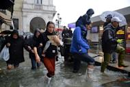 People walk in a flooded street during a 'acqua alta' or high water on November 11, 2012 in Venice. The authorities have urged the local population to avoid going into the streets and to stay in the the upper floors of their homes.