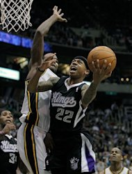 Sacramento Kings guard Isaiah Thomas (22) puts a shot up around the arm of Utah Jazz forward Paul Millsap, left, during the first half of their NBA basketball game in Salt Lake City, Friday, March 30, 2012. (AP Photo/Steve C. Wilson)