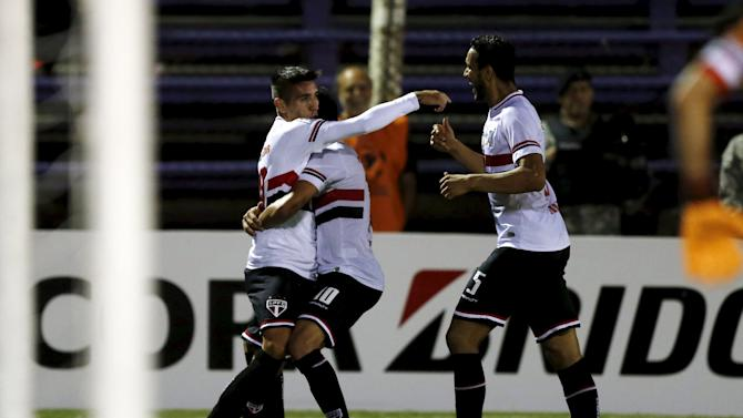 Ricky Centurion of Brazil's Sao Paulo is congratulated by teammates Ganso and Souza after scoring a goal against Uruguay's Danubio during their Copa Libertadores soccer match in Montevideo