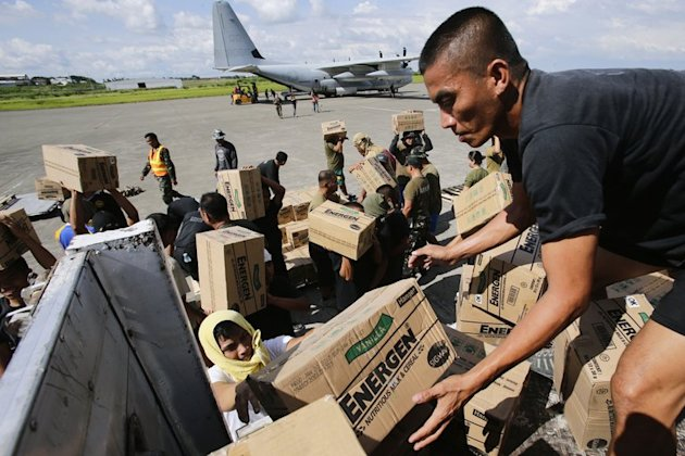 Philippine Army personnel unload relief goods at an airport in Mindanao on December 15, 2012. Typhoon Bopha killed 1,020 people, mostly on Mindanao island, where floods and landslides caused major damage on December 4, civil defence chief Benito Ramos said
