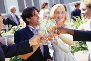 Bride and groom drinking with guests at wedding reception