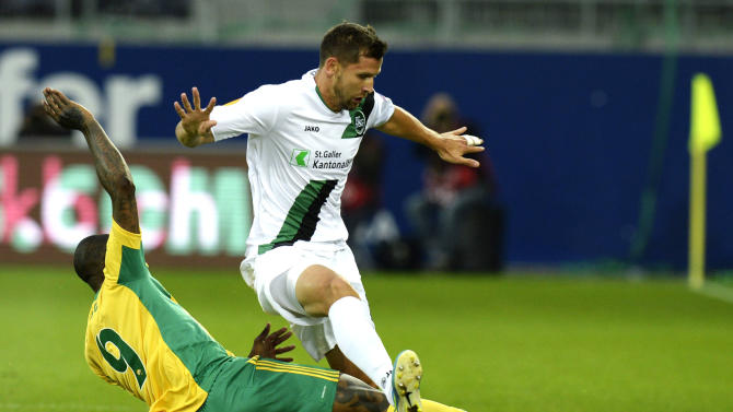FC St. Gallen's Stephane Besle, right, and Kuban Krasnodar's Djibril Cisse, left, challenge for the ball during their UEFA Europa League Group A  match between Switzerland's FC St. Gallen and Russia's Kuban Krasnodar at the AFG Arena in St. Gallen, Switzerland, Thursday, Sept.  19, 2013