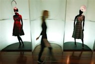 A woman walks past mannequins wearing creations once worn by Isabella Blow at the Isabella Blow: Fashion Galore! exhibition at Somerset House in London November 19, 2013. REUTERS/Suzanne Plunkett
