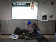 People sit on the floor and watch a movie on a computer as they wait for their delayed flight at La Guardia airport in New York January 6, 2014. REUTERS/Carlo Allegri