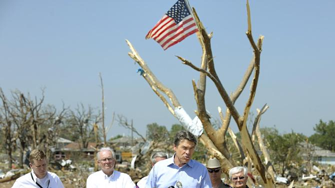 Texas Gov. Rick Perry, center, speaks to the media during a tour of storm damaged areas in Granbury, Texas, on Friday May 17, 2013. On Wednesday, powerful storms produced 16 tornadoes in the area that left six people dead. (AP Photo/The Fort Worth Star-Telegram, Max Faulkner)  MAGS OUT; (FORT WORTH WEEKLY, 360 WEST); INTERNET OUT