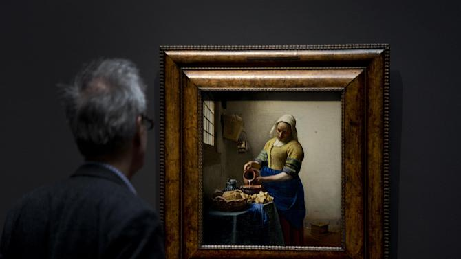 A man looks at Dutch master Johannes Vermeer's The Milkmaid painting (oil on canvas, circa 1660) during a press preview of the renovated Rijkmuseum in Amsterdam, Thursday April 4, 2013. The Rijksmusuem, home of Rembrandt's Night Watch and other national treasures, is preparing to reopen its doors on April 13, 2013 after a decade-long renovation. (AP Photo/Peter Dejong)