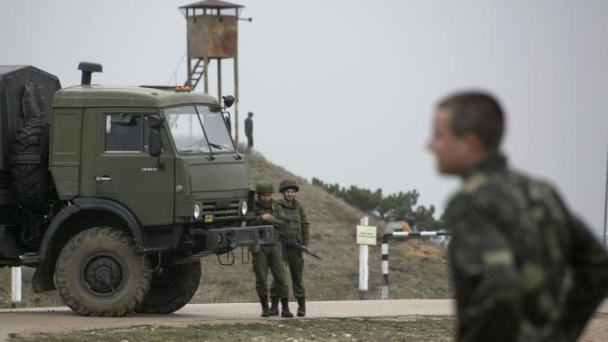Russian soldiers watch as Ukrainian serviceman play soccer at Belbek airport in the Crimea region