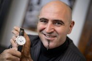 CEO of Swiss watchmakers Blancpain, Marc Hayek, poses with a Chinese-themed limited edition model of a watch which shows the Chinese time and calendar, as well as the signs of the zodiac and phase of the Moon