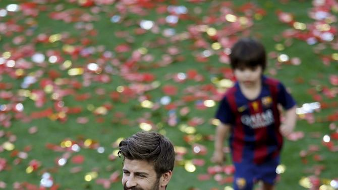 Barcelona's player Gerard Pique holds his son Sasha, followed by his older son Milan, during celebrations for winning the Spanish first division soccer league at Camp Nou stadium in Barcelona
