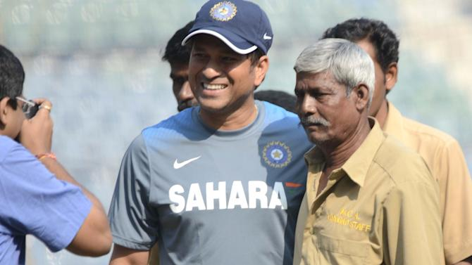 Master blaster Sachin Tendulkar with a ground staff as ground staffs members felicitated him ahead of his 200th and last test match at Wankhede Stadium in Mumbai on Nov.13, 2013. (Photo: Sandeep Mahankaal/IANS)