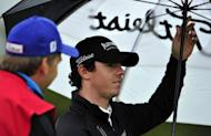 Rory McIlroy of Northern Ireland shelters from the rain during his first round on the opening day of the 2012 Open Championship at Royal Lytham and St Annes in Lytham