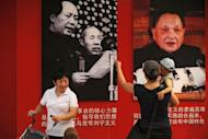 A mother shows her child pictures of former communist party leaders Mao Zedong (top L) and Deng Xiaoping (top R) in Ditan Park in Beijing in June 2011. Authorities in China's most populous province have asked Beijing to ease the one-child policy, a government official said Tuesday, amid growing concerns over gender imbalances and an ageing population