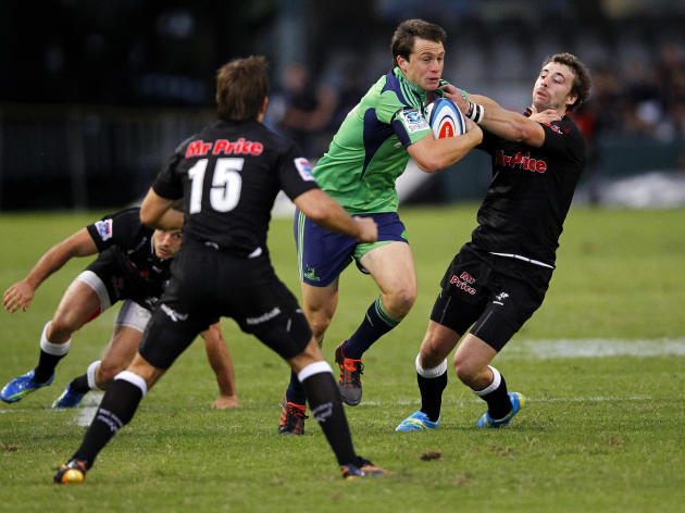 New Zealand Otago Highlanders' Ben Smith (R) tries to break a tackle from Durban Sharks' Tim Whitehead during the Super 15 Rugby Union match at the Kings Park Rugby Stadium in Durban on May 5, 2012.