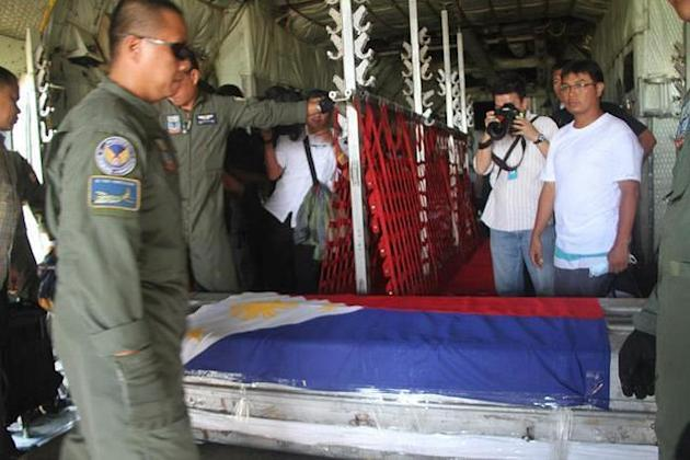 Members of the Philippine armed forces and National police carry the body of DILG Sec. Jesse Robredo placed inside a metal casket inside the Masbate airport on 21 August 2012. (HANDOUT PHOTO Philippine Air force, NPPA Images)