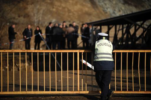 A Serbian police officer looks at Kosovo families and Forensic Department employees gathered for the first time at the site of a suspected mass grave in the village of Rudnica, Serbia, on December 28,