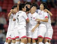 North Korea's Kim Song Hui (3rd L) celebrates scoring a goal against Colombia during a group G Olympic Women's football match at Hampden Park, in Glasgow, Scotland. North Korea's women's football team refused to take the field for more than an hour Wednesday in protest at an embarrassing mix-up of their national flag on day one of the London Olympics