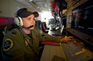 In this Wednesday, March 19, 2014 photo released by the Australia Defence Department, Royal Australian Air Force Airborne Electronics Analyst, Flight Sgt. Tom Stewart from 10 Squadron, on board an AP-3C Orion watches a radar screen over the Southern Indian Ocean off the Western Australian coast during a search operation for the missing Malaysia Airlines flight MH370. Australian Prime Minister Tony Abbott said Thursday that two objects possibly related to the missing flight have been spotted on satellite imagery in the Indian Ocean and an air force aircraft was diverted to the area to try to locate them. (AP Photo/Australia Defence Department, Hamish Paterson)