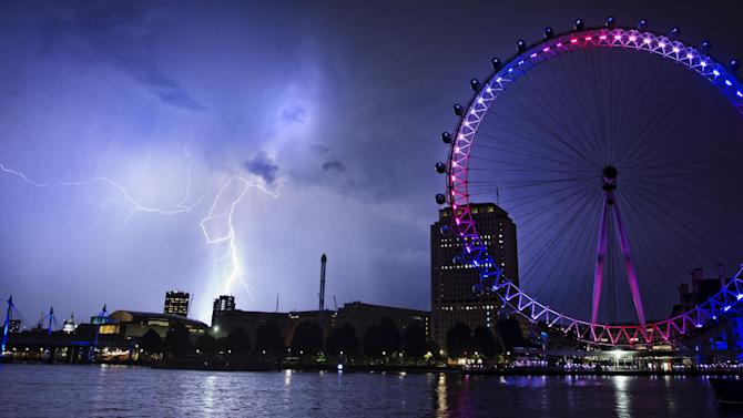 Lightning strikes behind The London Eye in central London which is lighted up in the national colors of red, white and blue to mark the birth of Prince William and his wife Kate's first child Tuesday, July 23, 2013. (AP Photo/PA, Lewis Whyld) UNITED KINGDOM OUT, NO SALES, NO ARCHIVES