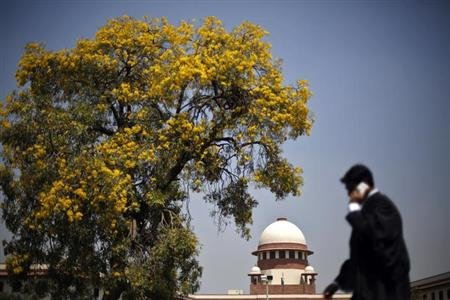 A lawyer speaks on his mobile phone as he walks past the Supreme Court in New Delhi April 1, 2013. REUTERS/Adnan Abidi/Files