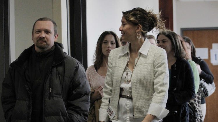 A victim assistance advocate, right front, escorts victims and family members to court for a hearing for Aurora theater shooting suspect James Holmes at the courthouse in Centennial, Colo., on Wednesday, April 10, 2013. (AP Photo/Ed Andrieski)