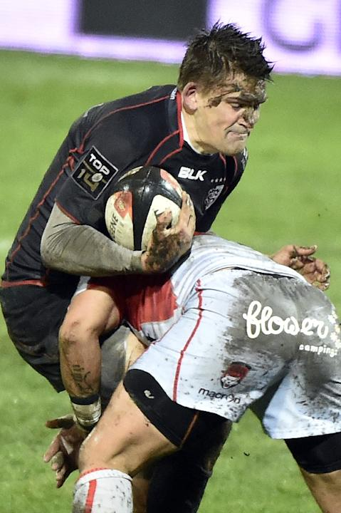 Toulouse's fly-half Toby Flood (L) is tackled during their French Top 14 rugby union match against Lyon, at the Ernest-Wallon Stadium in Toulouse, on February 21, 2015