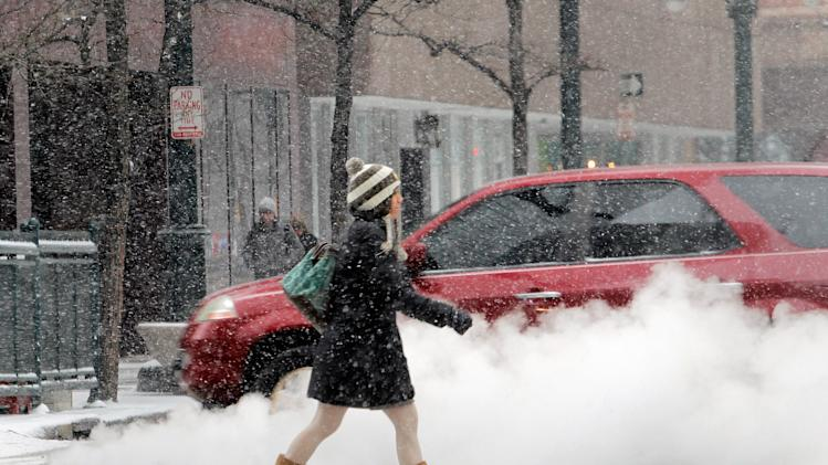 A woman crosses the street as steam rises from a manhole cover  in Denver's financial district  on Tuesday, April 9, 2013. A blizzard forecast for the area did not materialize. Instead as much as four inches of snow could fall on the Mile High City. (AP Photo/Ed Andrieski)