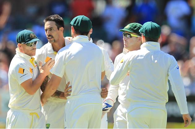 Australia's bowler Mitchell Johnson, second from left, celebrates with teammates after bowling South Africa's captain Graeme Smith, for 14 runs on the third day of their 2nd cricket test match