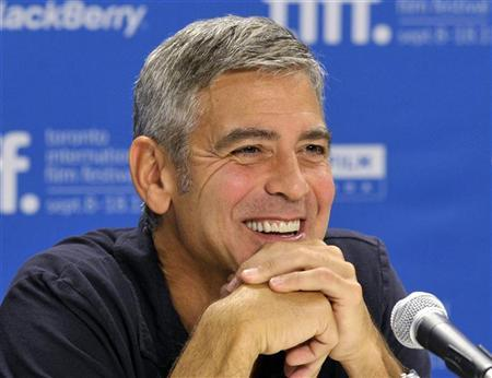 "Actor George Clooney smiles during the news conference for the film ""The Descendants"" at the 36th Toronto International Film Festival"