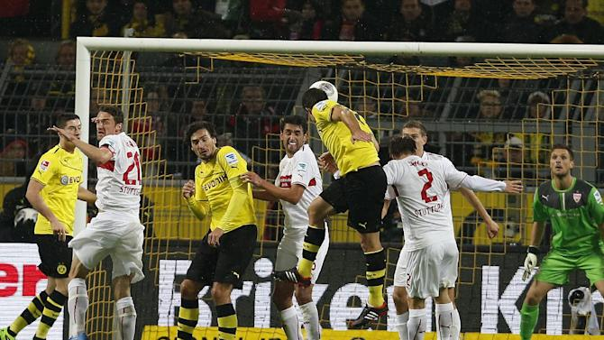 Dortmund's Sokratis of Greece, center, heads the ball to score  during the German first division Bundesliga soccer match between  BvB Borussia Dortmund and VfB Stuttgart  in Dortmund, Germany, Friday, Nov. 1, 2013