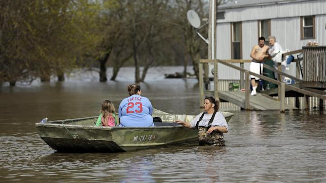 Julia Dowell pushes her daughter Barbara Adams and family friend Haley Wright, 4, at left, in a boat while Dowell's son Michael Dowell and mother Mary Niffer, right, watch from the porch of a trailer and Monday, April 22, 2013, in Clarksville, Mo. The swollen Mississippi River has strained a hastily erected makeshift floodwall in Clarksville, creating two trouble spots that volunteers were scrambling to patch. (AP Photo/Jeff Roberson)