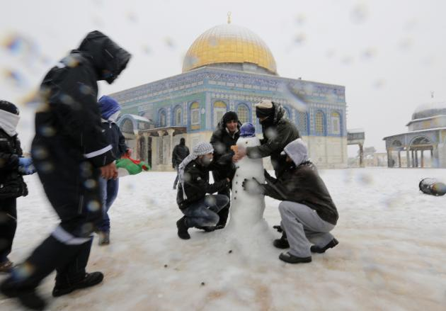 People build a snowman in front of the Dome of the Rock in Jerusalem's Old City