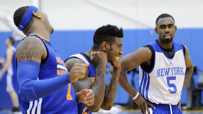 New York Knicks' Tim Hardaway, Jr. (5) looks on as Iman Shumpert and Carmelo Anthony, left, react to their shooting drill at the teams NBA basketball training camp Tuesday, Oct. 1, 2013, in Greenburgh, N.Y