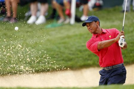 U.S. Team player Tiger Woods hits out of a bunker on the 12th hole during the second practice round for the 2013 Presidents Cup golf tournament at Muirfield Village Golf Club in Dublin, Ohio October 2, 2013. REUTERS/Chris Keane