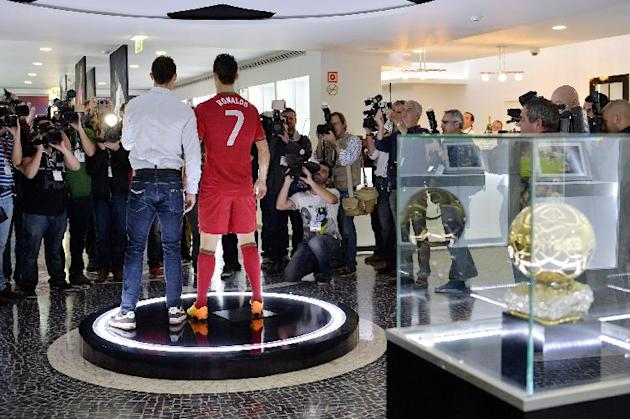 Cristiano Ronaldo, left, poses next to a model of himself wearing the Portuguese national team kit during a tour of his museum in Funchal, Portugal, Sunday, Dec. 15 2013. The museum which opened on Su