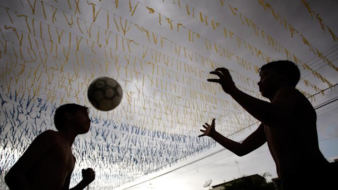 Boys play ball in a street decorated for the upcoming World Cup in Brasilia, Brazil, Friday, May 23, 2014. Brasilia is one of the host cities for the upcoming international soccer tournament that starts in June. (AP Photo/Eraldo Peres)
